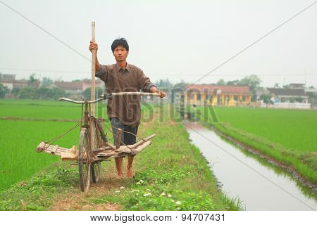 Nam Dinh, Vietnam - March 28, 2010: A Farmer In The North Of Vietnam Is Going To Work On His Paddy F