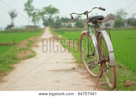 Nam Dinh, Vietnam - March 28, 2010: An Old Bike Parking On The Pathway Of The Paddy Field In The Nor
