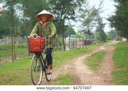 Nam Dinh, Vietnam - March 28, 2010: A Woman Farmer Is Biking Home From Her Work On The Paddy Field