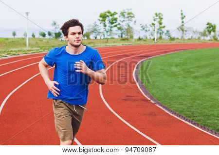 Young fit male in blue shirt running on a stadium running path
