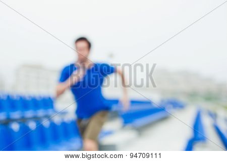 Unfocused runner in blue shirt running between blue stands on stadium
