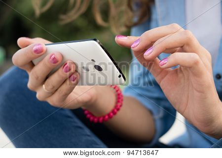 Women's Hands With Red Manicure Holding A Modern Mobile Phone With A Touch Screen