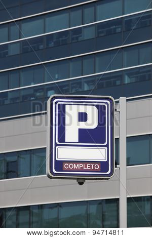 Parking Signpost With Completo Text And Modern Building Background