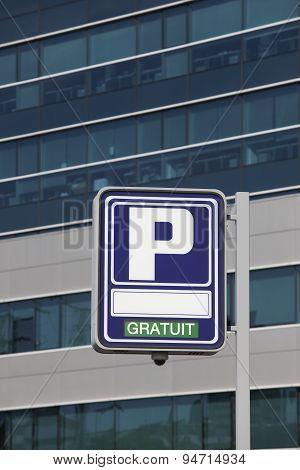 Parking Signpost With Gratuit Text And Modern Building Background