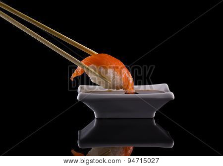 Salmon Sushi Nigiri In Hopsticks With Soy Sauce Over Black Background