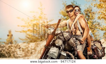 Sexy Couple Of Bikers With Guns On The Summer Background.