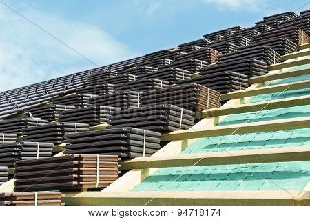 A roof under construction. Stacks of tiles ready to be fasten on the wooden construction. Waterproof and solid rooftop.