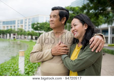 Hugging aged couple