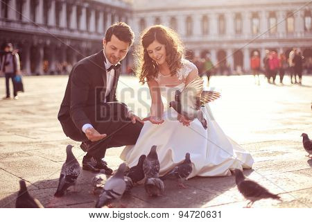 Bride And Groom Playing With Pigeons