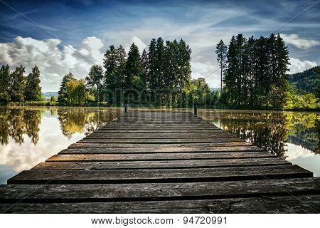 Wooden Footbridge In Front Of A Lake In Summer Season