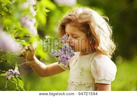 Girl Inhales The Aroma Of Lilacs