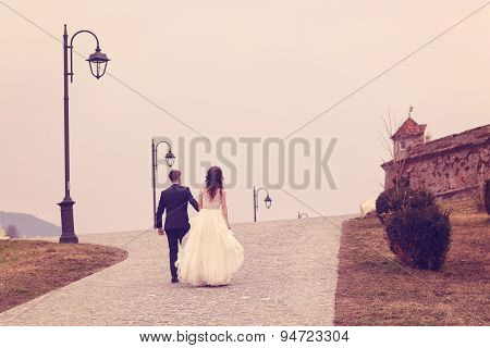 Bride And Groom Walking On Pavement