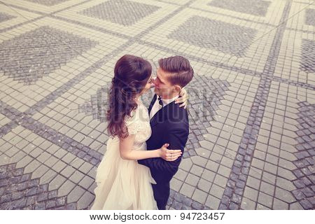 Bride And Groom Embracing On Paved Street
