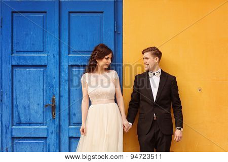 Bride And Groom Against Yellow Wall And Blue Door;
