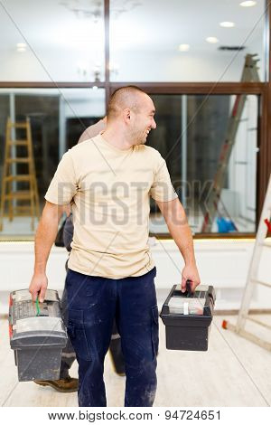Electrician Carrying Tool Boxes After Work