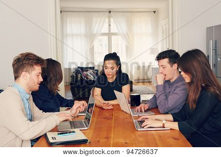 students learning at the table with laptops