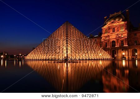 PARIS - APRIL 16: Reflection of Louvre pyramid shines at dusk during the Summer Exhibition April 16
