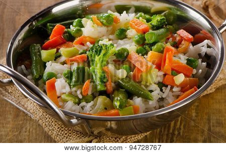Rice With Vegetables On A  Wooden Table.