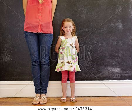 Little Girl With Sweet Smile Standing With Her Mother