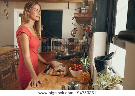 Pretty Young Woman In Kitchen Looking Away