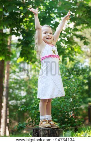 Little blonde girl standing with raised hands on tree stump full length