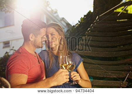 Romantic Young Couple In Hammock Toasting Wine