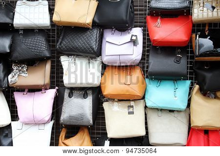 Women Handbags Hanging On Wall In Store