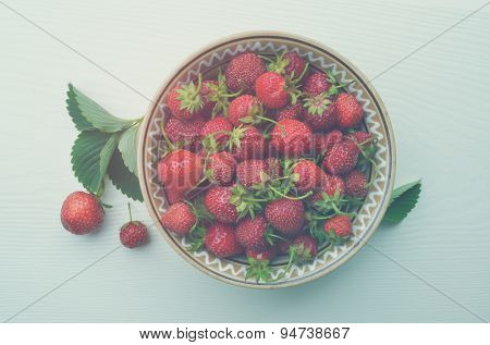 Ripe strawberries in a clay plate on a white wooden board. Top view. Color toning. Low contrast.