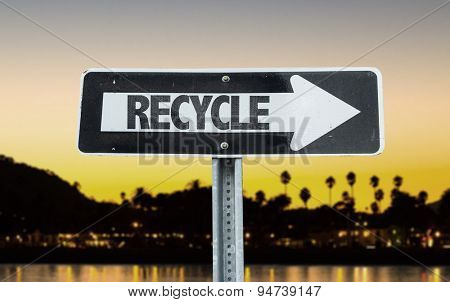 Recycle direction sign with sunset background