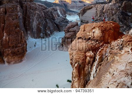Hikers in the rocky canyon in the desert. Two persons on top of the cliff and another two in the valley. Sinai, Egypt
