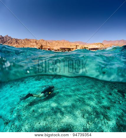 Split shot of the diver swimming underwater and desert coast of the South Sinai above the surface, Egypt