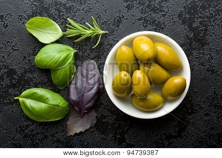 green olives and herbs on black table