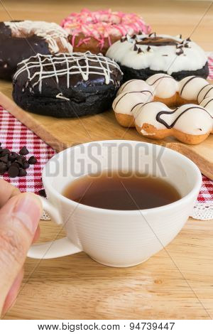 Hand Holding Cup Of Coffee During Doughnut Or Donut Coffee Break