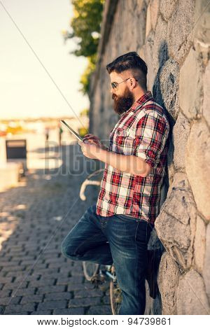 Trendy hipster young man using tablet. Posing next to stone wall