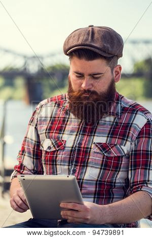 Trendy hipster young man portrait using tablet. Posing next to river