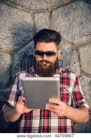 Trendy hipster young man portrait using tablet. Posing in front of stone wall