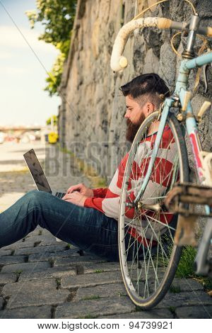 Trendy hipster young man with modern laptop. sitting in front of stone wall