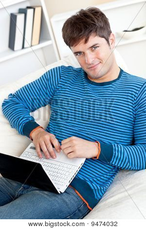 Cheerful Young Man Working On His Laptop Lying On The Couch
