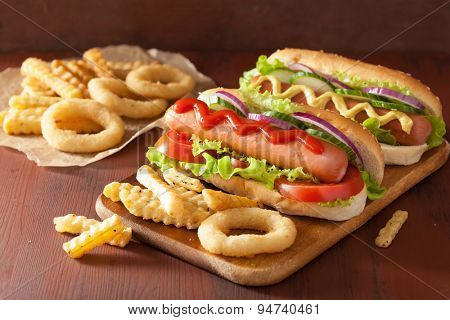 hotdog with ketchup mustard vegetables and french fries