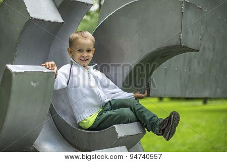 Cute funny little boy sitting on the Playground in a city Park.