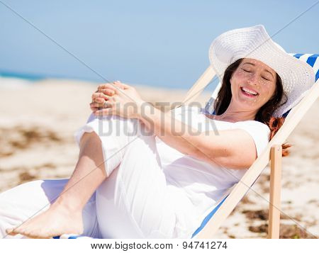 Woman in white clothes on the beach on sunny day