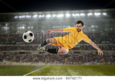 Soccer Player kicking the ball in a football stadium at night
