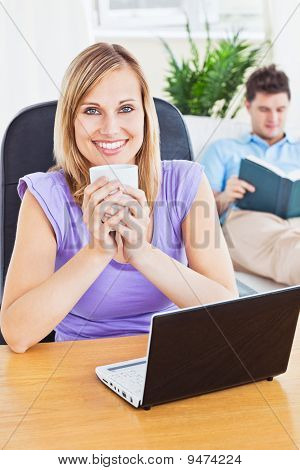 Beautiful Woman Drinking Coffee And Using Laptop While Boyfriend Is Reading A Book