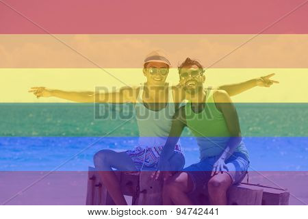 Celebrating marriage equality, male couple at the beach with the LGBT flag overlapped with medium opacity.