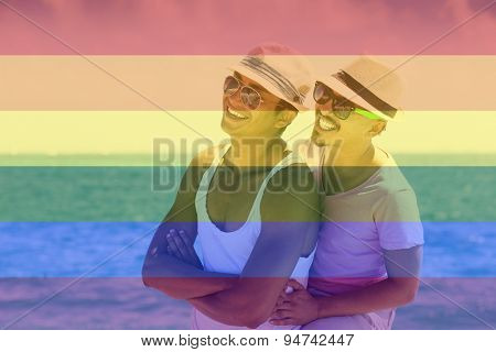 Celebrating marriage equality, couple in the Caribbean, laughing, hugging, looking to a side with the LGBT flag overlapped with medium opacity. . Isla Mujeres, Cancun, Mexico