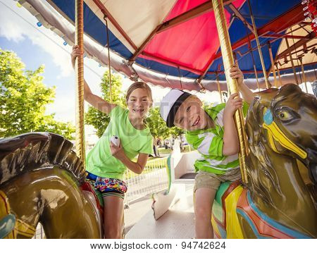 Cute kids having fun riding on a colorful carnival carousel