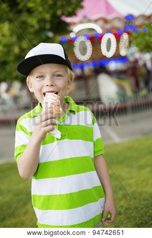 Cute little boy smiling and licking his ice cream at an outdoor carnival