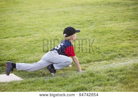 Young boy baseball player waiting on third base. He showing a funny sprinters stance