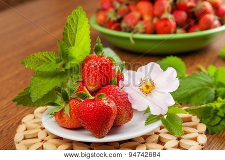 several strawberries on a plate on a table with a flower and mint. in the background a lot of strawberries