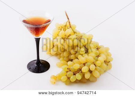 a large bunch of grapes with a glass of wine in the drops on a white background
